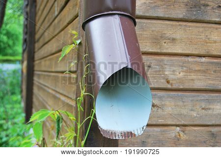 Pipe brown for drainage of rain water on the background of a wooden house