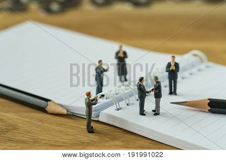 Miniature people small figure businessman handshaking and others clapping on notebook and pencil as business agreement concept.