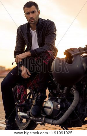 Handsome rider guy with beard and mustache in black leather biker jacket sit on classic style cafe racer motorcycle rooftop at sunset. Bike custom made in vintage garage. Brutal fun urban lifestyle.