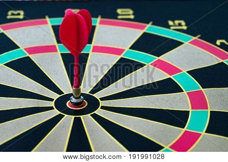 Business target and gold concept with a magnetic red dart pinned in the center of dartboard.