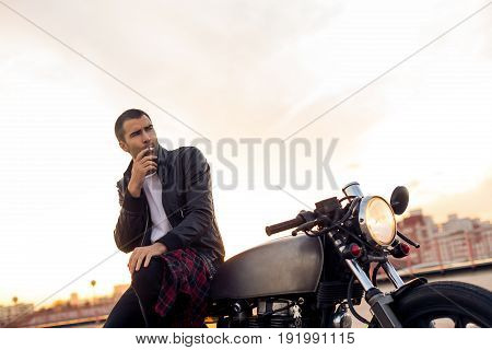 Handsome rider guy with beard and mustache in black biker jacket smoking while sit on classic style cafe racer motorbike at sunset. Bike custom made in vintage garage. Brutal fun urban lifestyle.