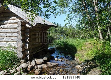 Log cabin at small brook near the lakeshore on the Big Solovetsky Island Russia. Sunny summer day.