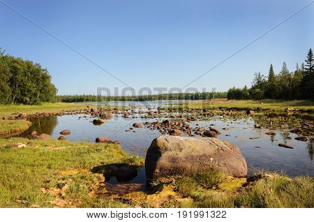 Large stones on the shore of the White Sea Bay during the low tide Bolshoy Solovetsky Island sunny summer day