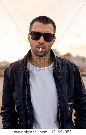 Close up of a handsome rider man with beard and mustache in black biker jacket fashion sunglasses smoking cigaret near classic style cafe racer motorbike at sunset. Brutal urban lifestyle portrait.