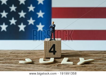 Independence day USA with miniature figure businessman standing on wooden cube number 4 and alphabets JULY on wood table and United State national flag in the background.