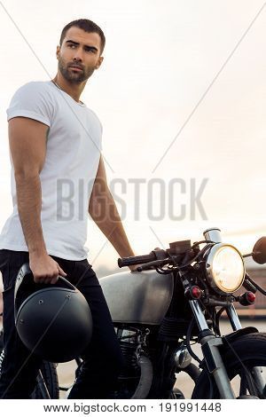 Sporty biker handsome rider male in white t-shirt hold black helmet near classic style cafe racer motorbike at sunset. Vintage bike custom made in garage. Brutal urban lifestyle. Outdoor portrait.