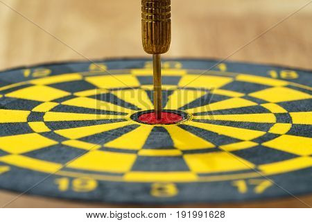 Business goal or target concept with a gold needle dart in the center of dartboard.