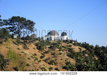 The Griffitth observatory in Los Angeles California on the hillside on a sunny afternoon.