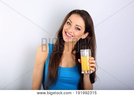 Beautiful Happy Young Healthy Casual Woman Holding The Glass With Orange Juice In The Hand On Blue B