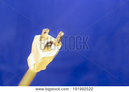 White Electrical Plug and Cord Isolated on Blue Background