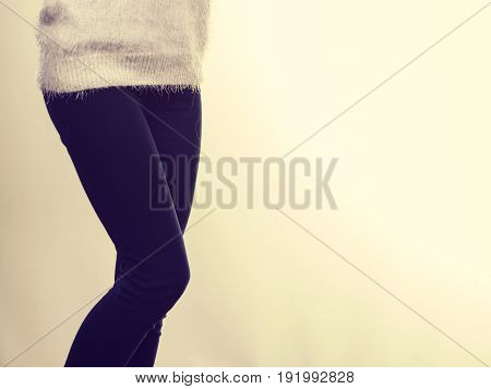 Winter fashion outfit ideas concept. Woman legs in black leggings trousers and grey furry jumper.