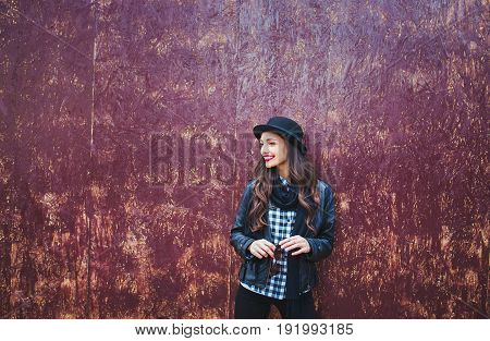 Young stylish woman in a city street. beautiful brunette girl walking around the city.leather jacketurban backpack bright red lips and hat