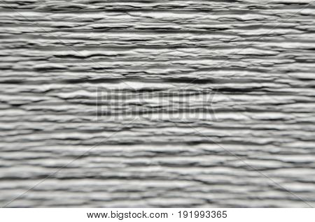 Blur white texture of embossed paper. Macro. Shallow depth of field. Abstract blur background with deep grooves in the texture of corrugated paper. Pattern of horizontal grooves