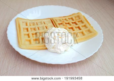 belgian waffles with cream on a white plate
