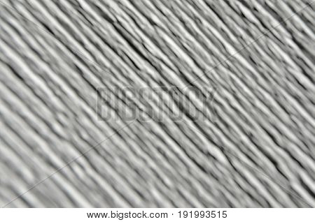 White texture of embossed paper. Macro. Shallow depth of field. Abstract background with deep grooves in the texture of corrugated paper. Pattern of lines on a diagonal