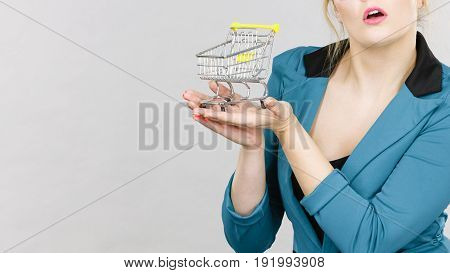 Buying things at market shops concept. Business woman hand holding small tiny shopping cart trolley