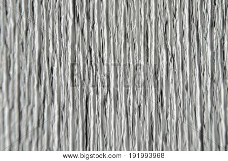 White texture of embossed paper. Macro. Shallow depth of field. Abstract background with deep grooves in the texture of corrugated paper. Pattern of vertical grooves