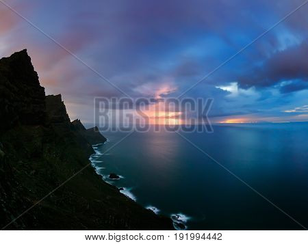 view of Gran Canaria sttep cliffs of western coast from Mirador del Balcon, sunset with stormy clouds and lightnings