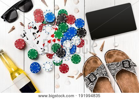 Card deck surrounded by poker chips and scattered seashells, glasses, a tablet and bottle of beer, on white wooden background with copy space
