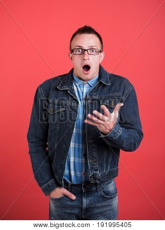 surprise on face of man in nerd glasses shirt and jeans jacket on red background with hands in pocket denim style beauty and fashion student lifestyle