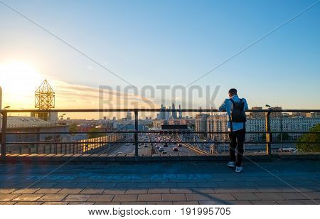 Photographer taking picture above Moscow cityscape with Third Transport Ring road and modern architecture of Moscow City Business Center, Russia. Phrase on asphalt I love you too in Russian