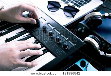 Music producer is producing Music on synthesizer keyboard