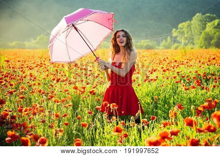 summer. umbrella pink color at pretty happy girl with long curly hair in red dress in field of poppy seed flower on green stem on natural background drug and love intoxication opium