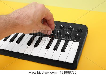Musical instrument - Hand control MIDI keyboard on a flavovirent background.