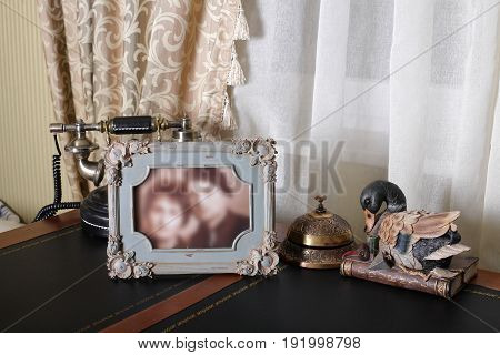 Retro style. Vintage phone and frame on a wooden classical table.