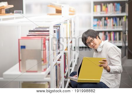 Young Asian man university student reading book in library education research and self learning in college life concepts