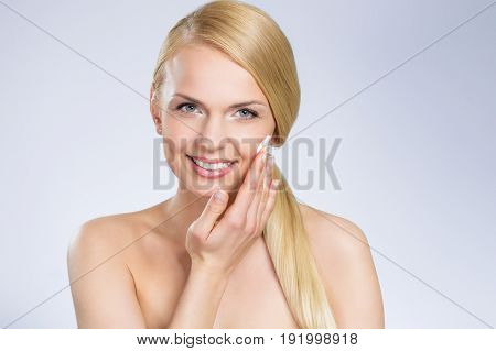 Young Pretty Woman Applying Cream On Face