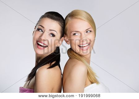 Two Beautiful Happy Women Leaning On Each Other Back