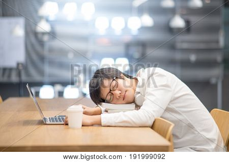 Young Asian university student take a nap on book stack during doing homework in library college lifestyle concepts