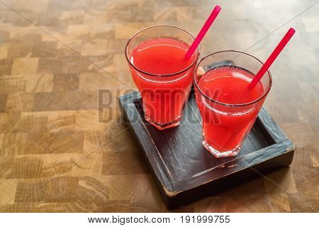 Two glasses of sweet fresh strawberry juice on the wooden table