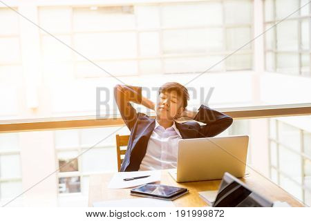 Asian short black hair tomboy business with two hand on head sit in front of laptop and close her eyes.