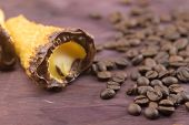 delicious sicilian cannolo cannellino sweet with pastry hazelnut chocolate and pastry cream near coffee beans italian puff-pastry on wood background nutrition and diet concept poster