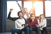 happy multicultural teenagers playing video games with joysticks at home teenagers having fun concept poster