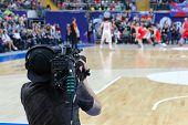 Cameraman works at basketball game in big stadium, back view poster