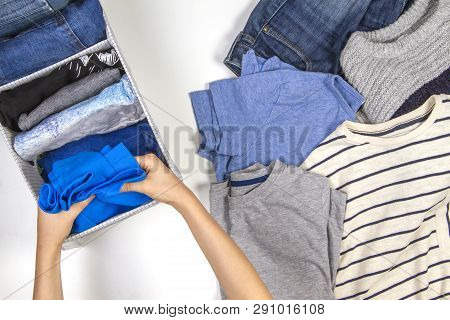 Vertical Storage Of Clothing, Tidying Up, Room Cleaning Concept. Hands Tidying Up And Sorting Kids C