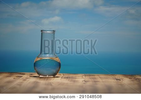 Clean water in a glass laboratory flask on wooden table on blue sea background. Ecological concept, the protection of water resources, the test of purity and quality of water.
