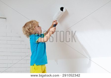 Kids Painting Attic Wall. Home Improvement And Renovation. Child Applying White Paint On Brick Walls