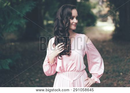 Cute feminine young brunette with curls in a pink dress in the park, the personification of tenderness and femininity poster