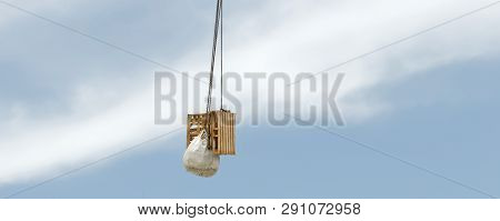 A Working Crane With Cargo Lifted High In A Cumulus Cloudy Sky. Industry Blue Sky Background Image W