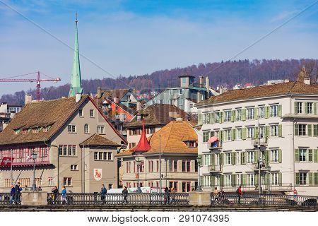 Zurich, Switzerland - March 22, 2019: People On The Munsterbrucke Bridge, Buildings Of The Historic