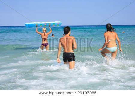 Group of three friends - man and women - on the beach having lots of fun in their vacation in Greece
