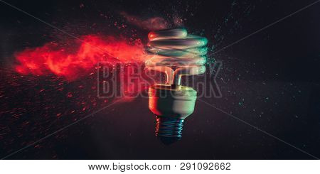 Studio photography of the real explosion of a low-consumption light bulb shot at the exact moment of the impact with a bullet. Gases and glasses are visible when moving.  Concept of obsolescence.