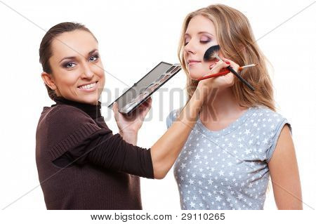 professional esthetician applying eyeshadow from color palette. isolated on white background