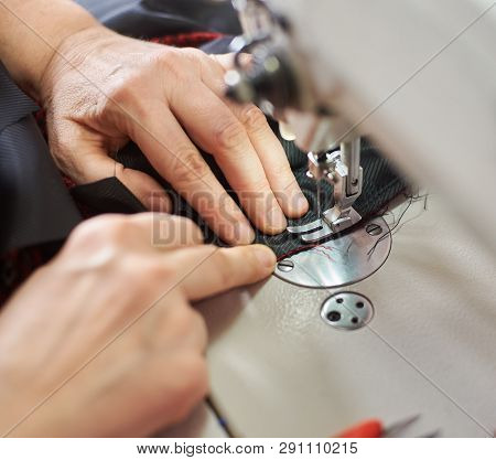 Top View Of Woman Hands Stitching Garment On Professional Sewing Machine At Workplace. Tailor Hands