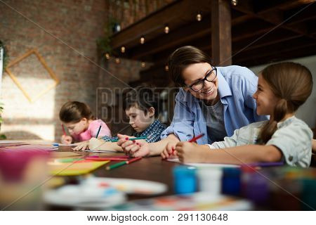 Portrait Of Smiling Young Woman Working With Kids In Art Class, Copy Space