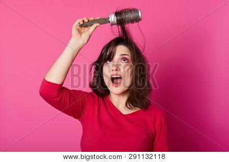 Adorable Woman With Brown Tangled Hair Tries To Comb Hairs, Looks Up, Wants To Blow Out Comb And Doi